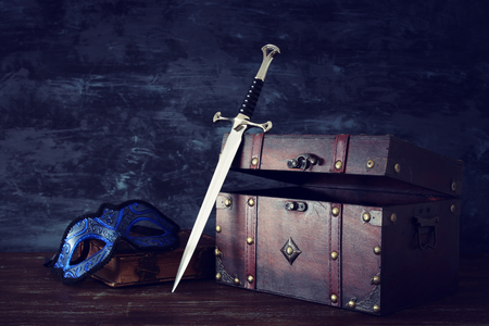 Low key image of open chest, mysterious mask over antique old book and sword. Fantasy medieval period Stock Photo