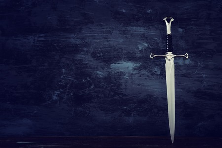 Low key banner of silver sword and old wooden chest. Fantasy medieval period Stock Photo