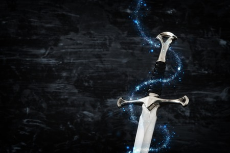 Low key image of silver sword with magical lights. Fantasy medieval period Stock Photo