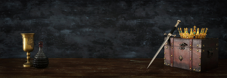 Low key banner of beautiful queenking crown, wine cup and sword. Fantasy medieval period Stock Photo
