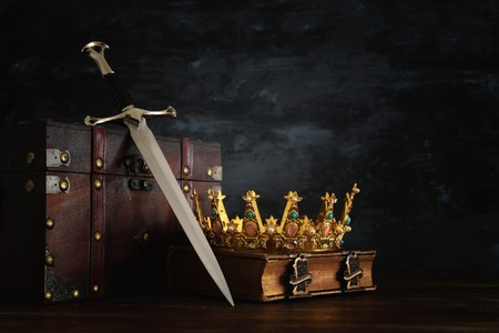 Low key image of beautiful queenking crown over antique book, chest and sword. Fantasy medieval period Stock Photo