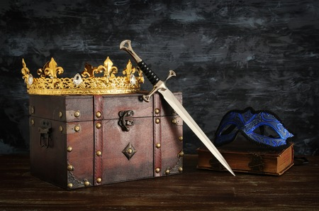 Low key image of beautiful queenking crown, mysterious mask and sword. Fantasy medieval period