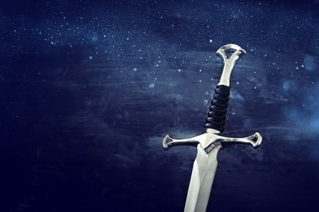 Low key image of silver sword. fantasy medieval period. Glitter overlay Stock Photo