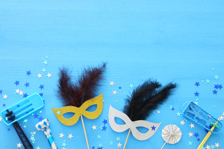 Purim celebration concept (jewish carnival holiday) over blue wooden background. Top view