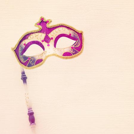 carnival party celebration concept with elegant gold, pink and purple mask on stick over white wooden background. Top view