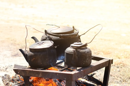 Cooking food in a rustic old kettle on bonfire in the forest