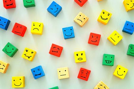 koncepcja różnych emocji rysowanych na kolorowe kostki, drewniane tła. Zdjęcie Seryjne