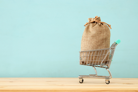 shopping cart with full bag full over blue wooden background