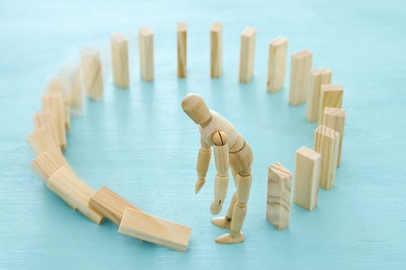 Thoughtful confused wooden dummy building circle domino puzzle and making mistake