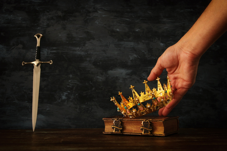 low key photo of king holding gold crown and sword. fantasy medieval period 版權商用圖片