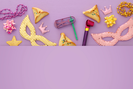 Purim celebration concept (jewish carnival holiday) over purple, pink wooden background. Top view