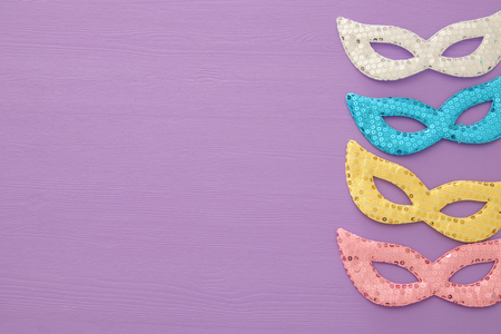 carnival party celebration concept with colorful pastel pink, gold, silver and blue masks over purple wooden background. Top view Stock Photo