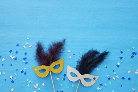 Carnival party celebration concept with masks blue wooden background. Top view