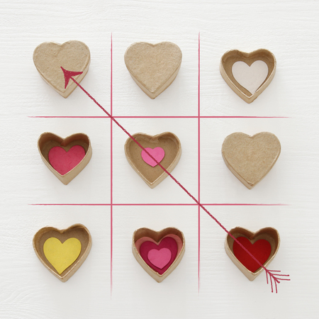 Valentines day concept with paper gift boxes as hearts. X-O game. Top view over wooden white bakground Stock Photo