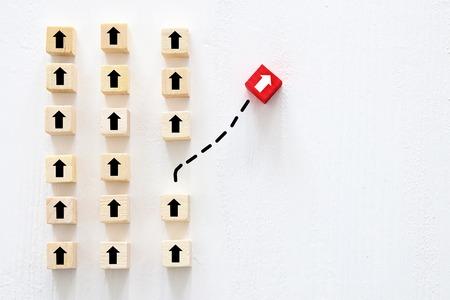 Koncepcja myślenia odmiennego, innowacji i kreatywności. Czerwona kostka zmienia kierunek od innych