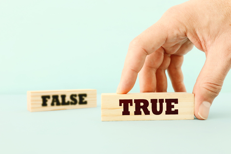 true or false concept man hand picking wooden cubes with text over wooden blue background Stock Photo