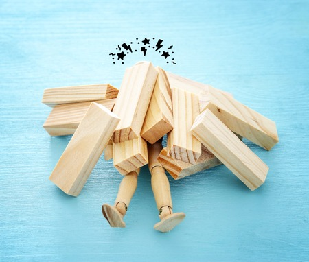wooden dummy buried under stack of domino blocks asking for help. concept of stress, trouble and deadline overwork