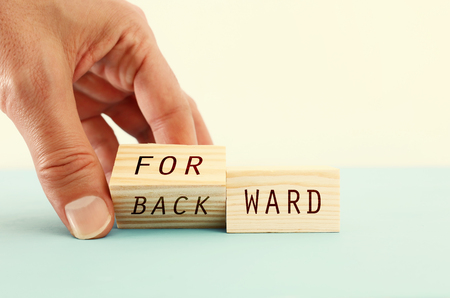 person hand flipping wooden cubes so that it will be written forward instead of backward. personal development and positive thinking concept