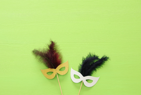carnival party celebration concept with silver and gold masks over green wooden background. Top view