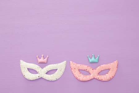 carnival party celebration concept with colorful masks over purple wooden background. Top view