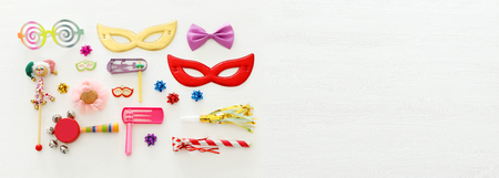 Purim celebration concept (Jewish carnival holiday) over wooden white background. Banner Stock Photo