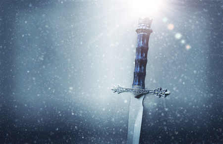 Mysterious and magical photo of silver sword over gothic snowy black background. Medieval period concept 版權商用圖片