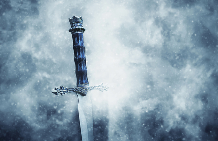 Mysterious and magical photo of silver sword over gothic snowy black background. Medieval period concept Stock Photo