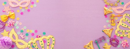Purim celebration concept (Jewish carnival holiday) over wooden purple background. Banner