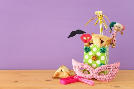 Purim celebration concept (jewish carnival holiday) over wooden table and purple background