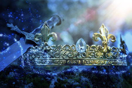 mysterious and magical photo of silver king crown and sword over the stone covered with moss in the England woods or field landscape with light flare. Medieval period concept