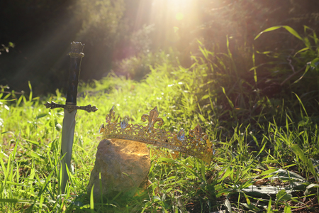 mysterious and magical photo of silver sword next to king gold crown in the England woods or field landscape with light flare. Medieval period concept
