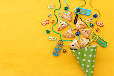 Purim celebration concept (jewish carnival holiday) over wooden yellow background 写真素材