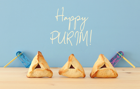 Purim celebration concept (jewish carnival holiday). Traditional hamantaschen cookies over wooden table and blue background Stock Photo