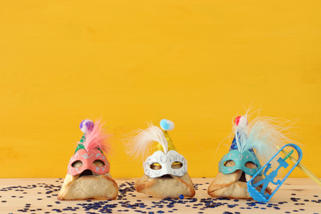 Purim celebration concept (jewish carnival holiday). Traditional hamantaschen cookies with cute clown hats and masks over wooden table