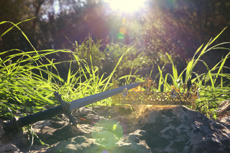 mysterious and magical photo of silver king crown and sword over the stone in the England woods or field landscape with light flare. Medieval period concept Banque d'images