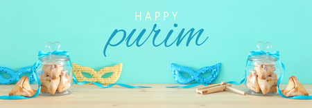 Purim celebration concept (jewish carnival holiday) over wooden table and mint background