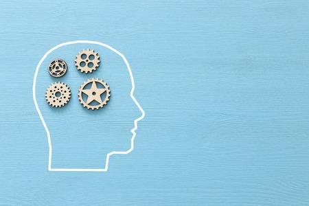 Gehirnstörung aus Holzzahnrädern in den menschlichen Kopf. Konzept der Alzheimer-Krankheit, Gedächtnisverlust, Zwangsstörungen, ADHS, Angststörungen und Thema der psychischen Gesundheit