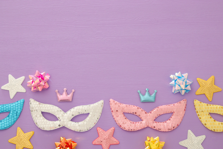 Carnival party celebration concept with colorful masks over purple wooden background. Top view. Flat lay Stock Photo