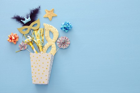Carnival party celebration concept with mask and colorful party accessories over blue wooden background. Top view. Flat lay.