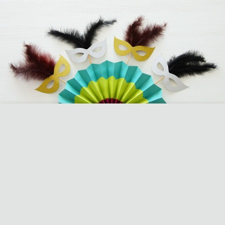 Carnival party celebration concept with masks and colorful fan over white wooden background. Top view - Image