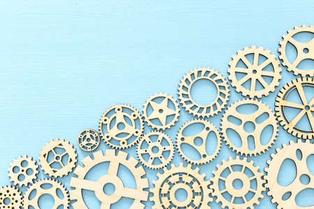 Working system of cogwheels, teamwork, flat lay, pastel yellow background