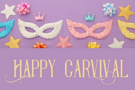 Carnival party celebration concept with colorful masks over purple wooden background. Top view. Flat lay Stockfoto