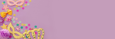 Carnival party celebration concept with mask and colorful party accessories over purple wooden background. Top view. Flat lay