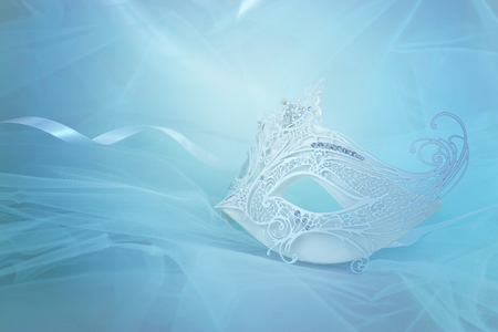 Photo of elegant and delicate white lace venetian mask over blue chiffon background
