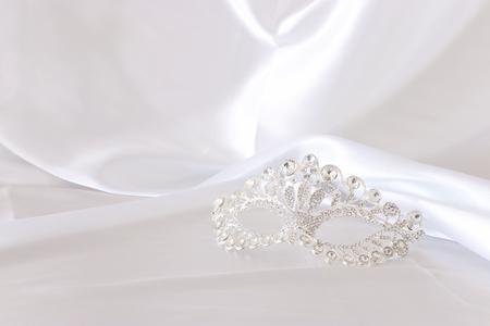 Photo of elegant and delicate silver diamond venetian mask over white silk background Stock Photo
