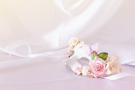 Photo of elegant and delicate white venetian mask with pink floral decorations over silk background
