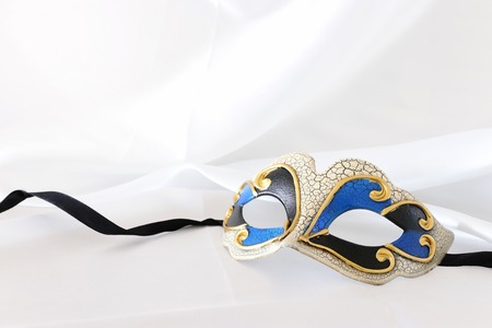 Photo of elegant and delicate venetian mask over white silk background