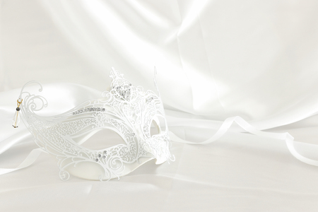 Photo of elegant and delicate white lace venetian mask over silk background