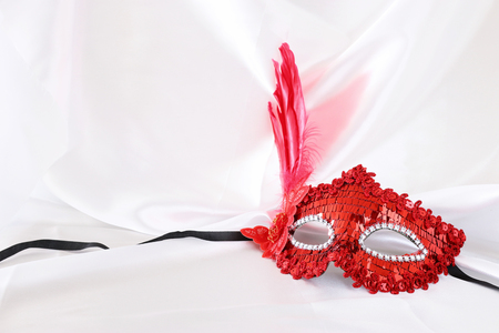 Photo of elegant and delicate red venetian mask over white silk background