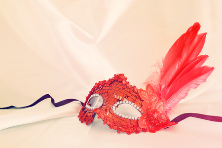 Photo of elegant and delicate red venetian mask over white silk background. Vintage filterd